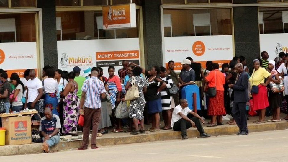 People queue to withdraw money from a bank in Harare (08 March 2017)