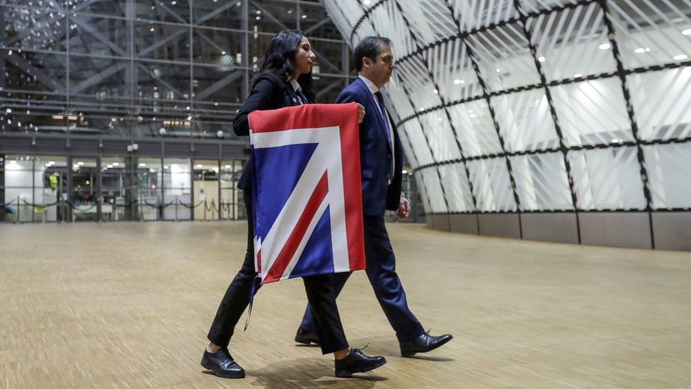 EU Council staff members remove the United Kingdom's flag from the European Council building in Brussels on Brexit Day, January 31, 2020