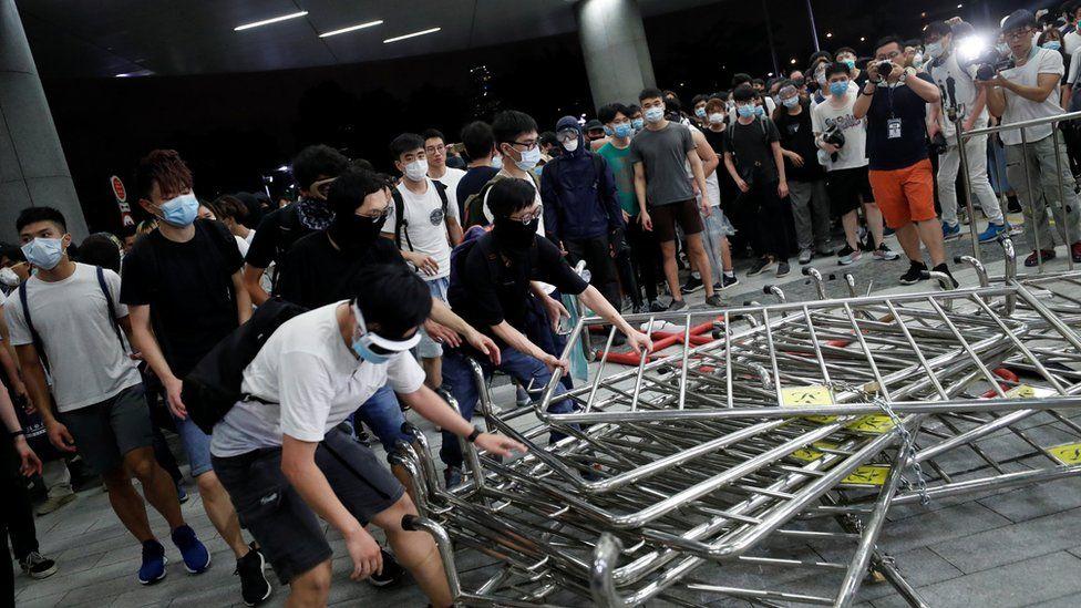 戴着口罩的示威者组拉倒香港立法会大楼门前的铁马(10/6/2019)