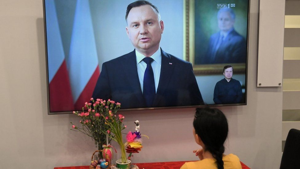 A woman watches Polish President Andrzej Duda delivering an address on a TV screen on 10 April marking the anniversary of the death of President Lech Kaczynski in a plane crash