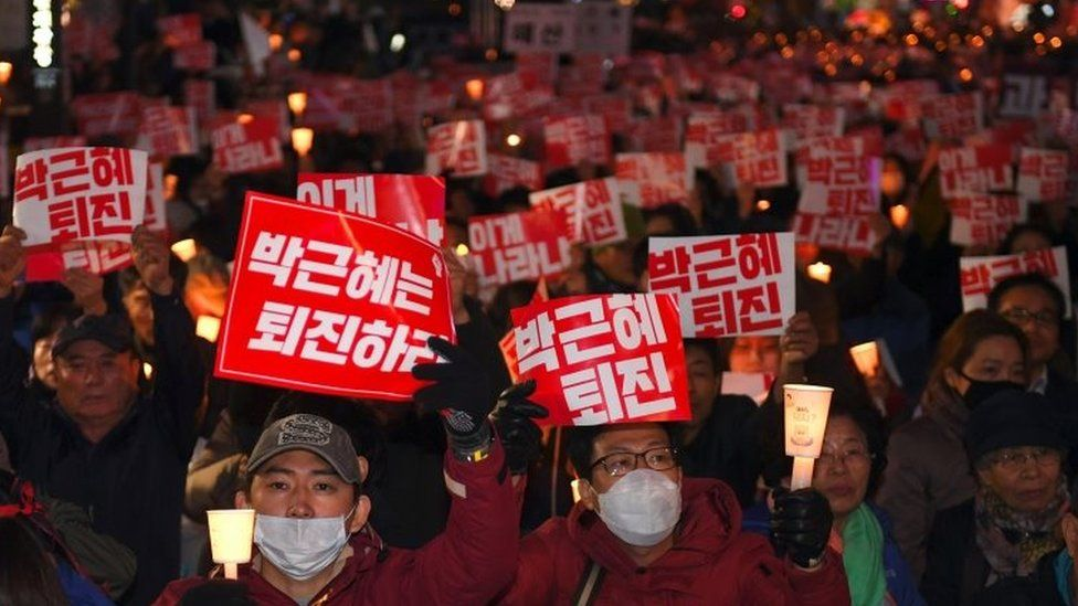 """Protesters in Seoul hold banners that read: """"Step down, Park Geun-hye"""""""