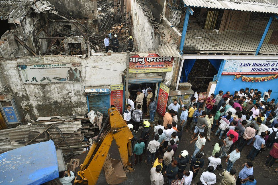 Indian policemen inspect a sweet shop destroyed by a fire on 18 December in Mumbai.
