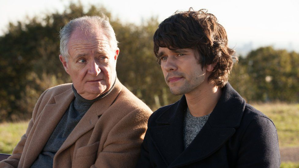 Jim Broadbent and Ben Whishaw sit on a bench in a London park