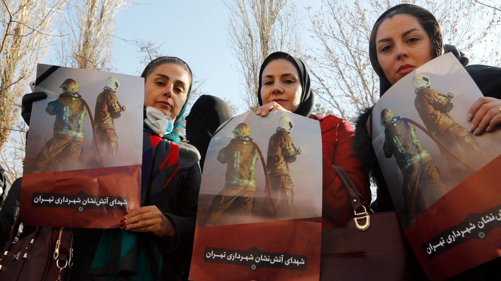 Women hold up posters honouring Iranian firemen who were killed in the Plasco building collapse in Tehran (30 January 2017)