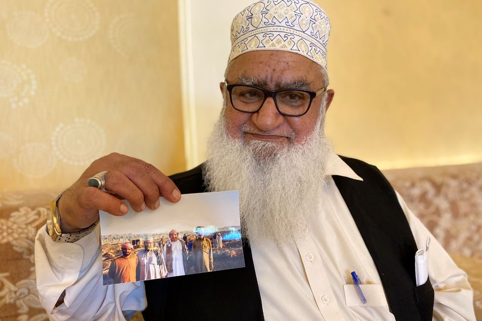 Haji Hanif showing a picture of a hunting party from the 1980s