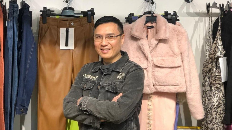 Johnny Tseng in front of fashion pieces he sells to UK labels including a pink furry coat and camel trousers