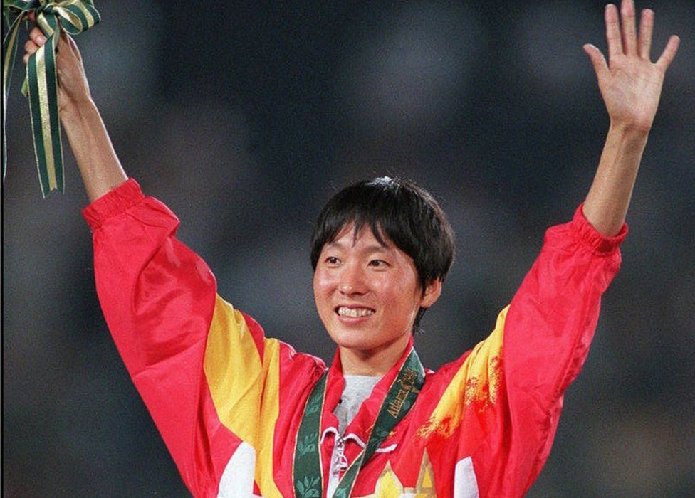 Wang Junxia from China celebrates on the podium during the medal ceremony after winning the gold medal in the women's Olympic 5,000m event at the Olympic Stadium in Atlanta, Georgia, 28 July 1996