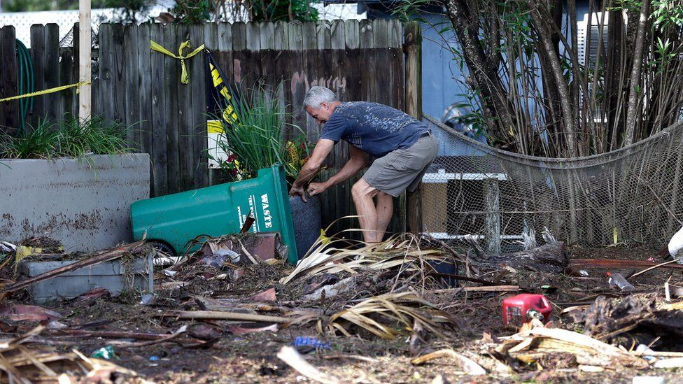 A business owner clears debris outside his office after Hurricane Hermine passed through Friday, 2 September 2016, in Cedar Key, Florida