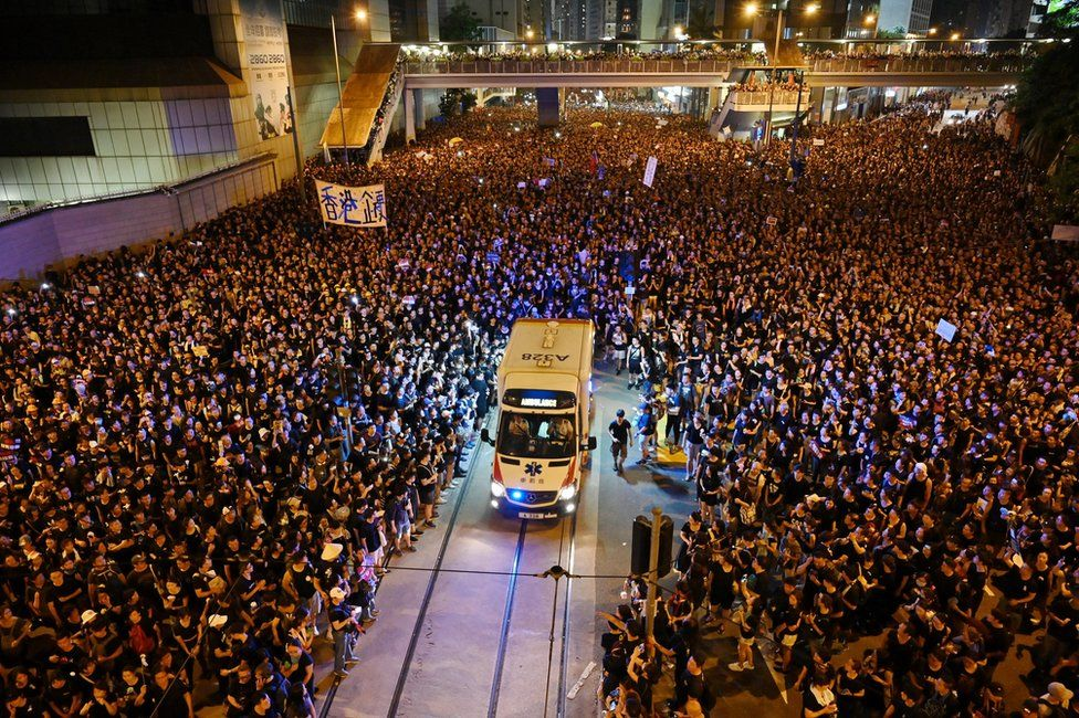 An ambulance is pictured surrounded by thousands of protesters dressed in black during a new rally against a controversial extradition law proposal in Hong Kong on 16 June 2019