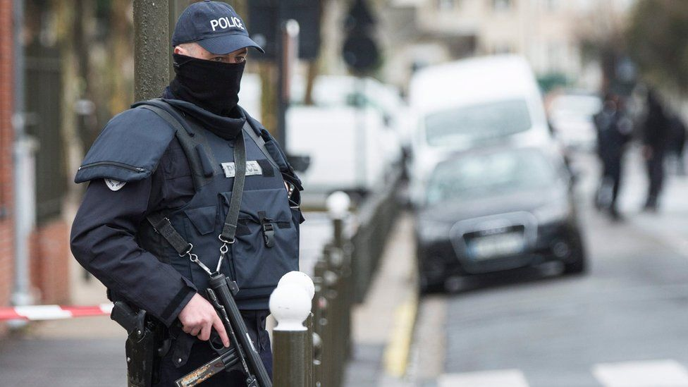 Police officer stands outside a building where an operation took place in Argenteuil, near Paris