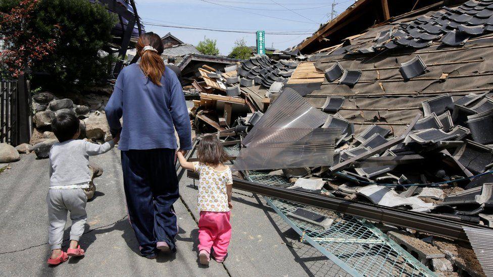 Survivors walk past debris
