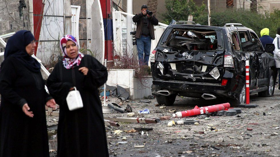 Women stand near a car damaged in a car bomb attack in eastern Baghdad (12 January 2016)