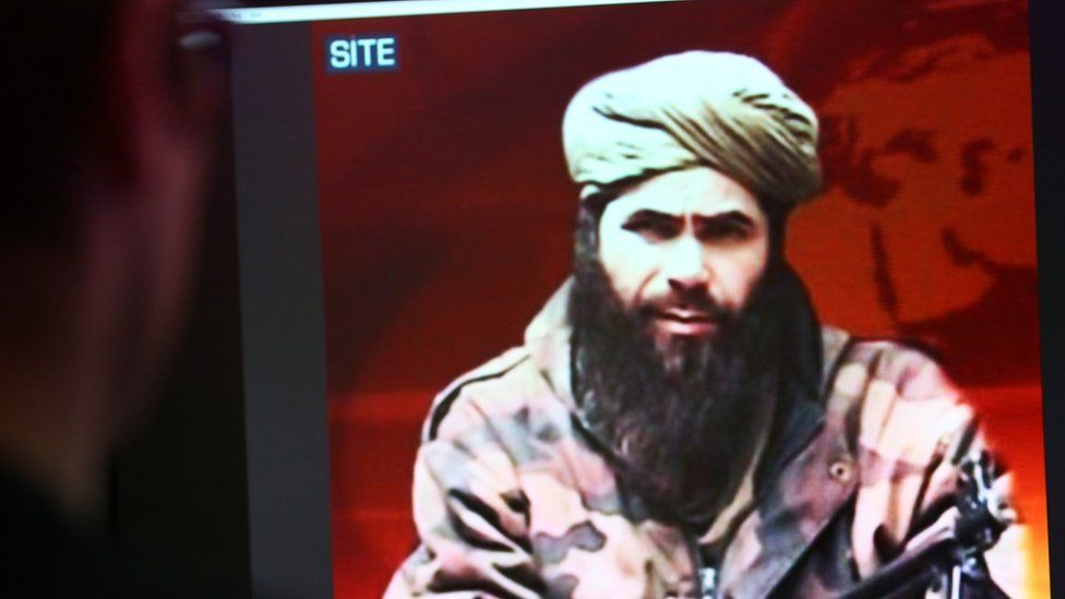 A man looks at a picture of Abdelmalek Droukdel, leader of AQIM