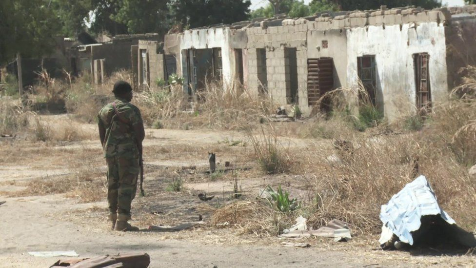 A soldier facing a destroyed building in north-east Nigeria