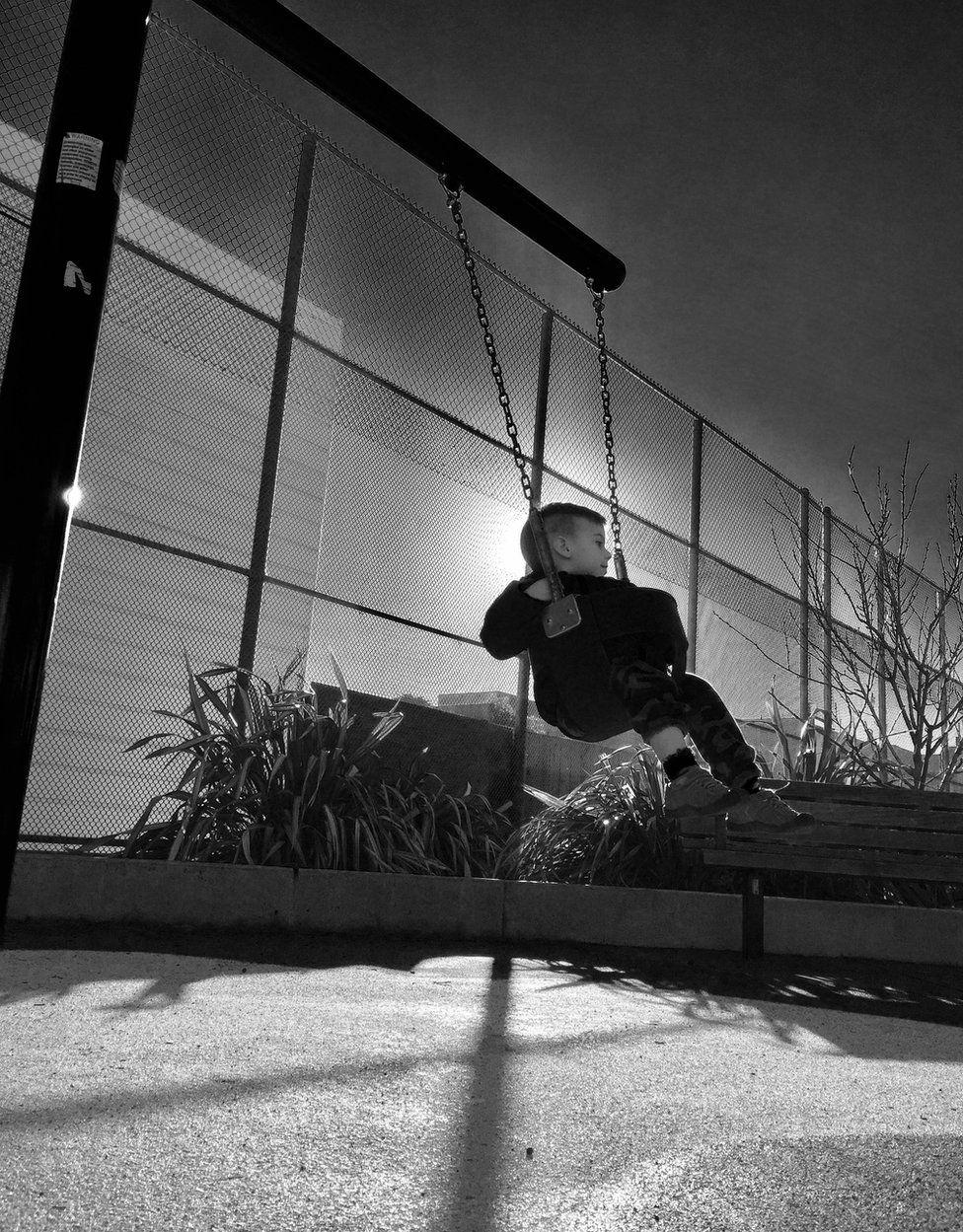 A boy plays on a swing