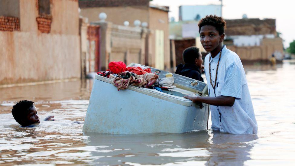 Someone rescuing a washing machine in floods near Khartoum, Sudan - September 2020