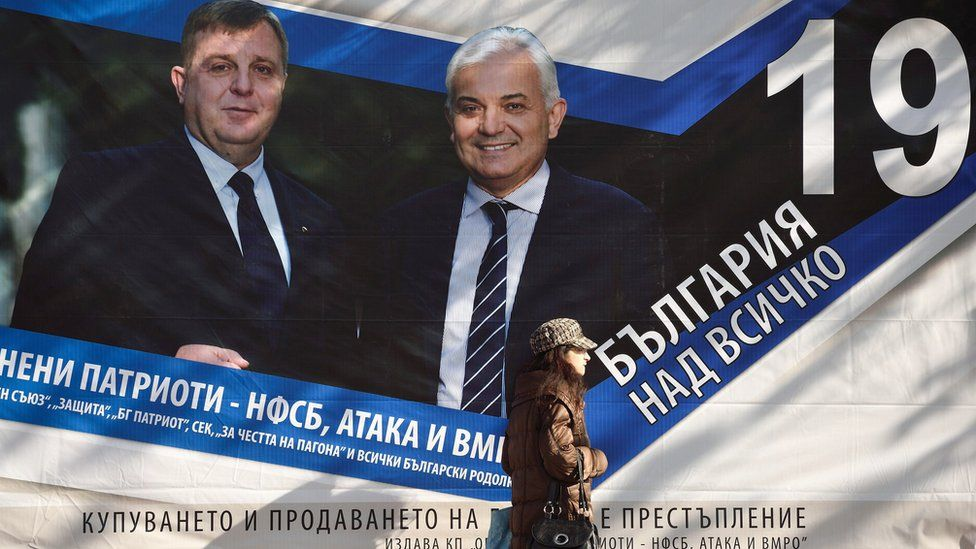 """A woman passes campaign posters of Presidential and vice candidate of Bulgaria""""s Coalition of Nationalist parties Krasimir Karakachanov (L) and Yavor Notev in Sofia, Bulgaria, 02 November 2016."""