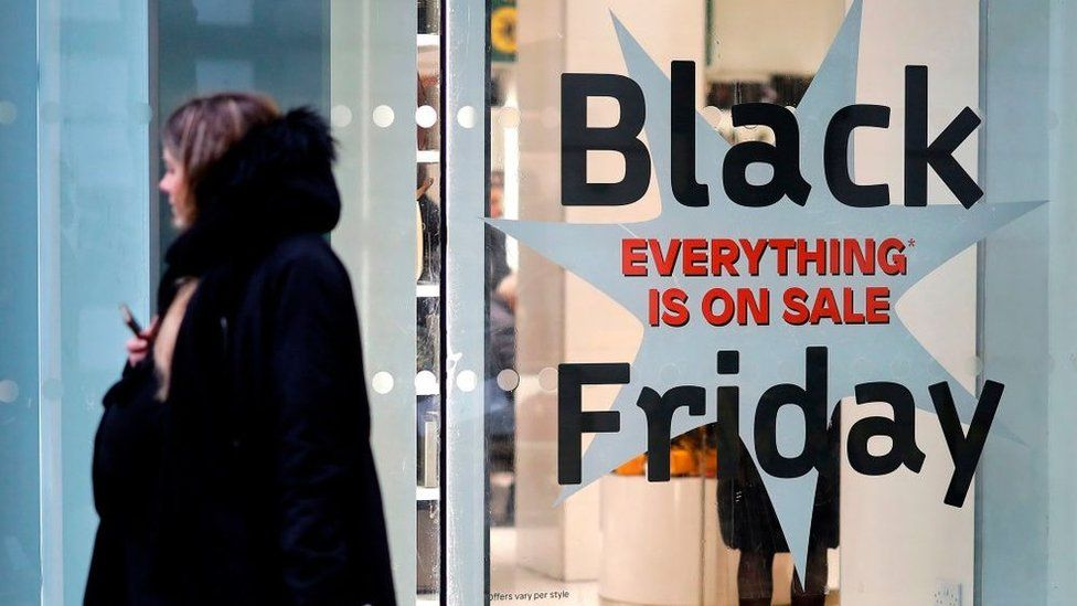 Shoppers pass a promotional sign for 'Black Friday' sales discounts, outside a store on Oxford Street in London, on November 26, 2019