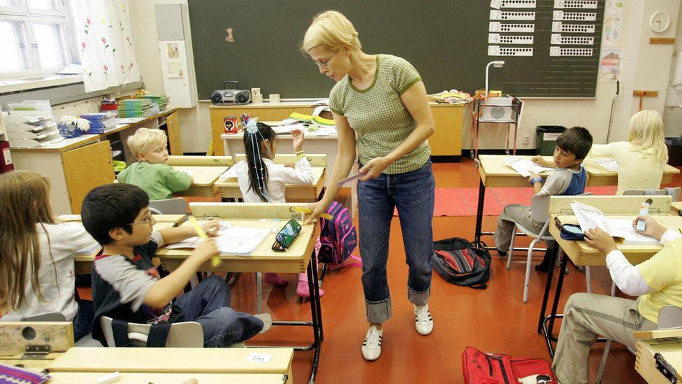 A teacher hands rulers to children in a primary school in Vaasa, Finland