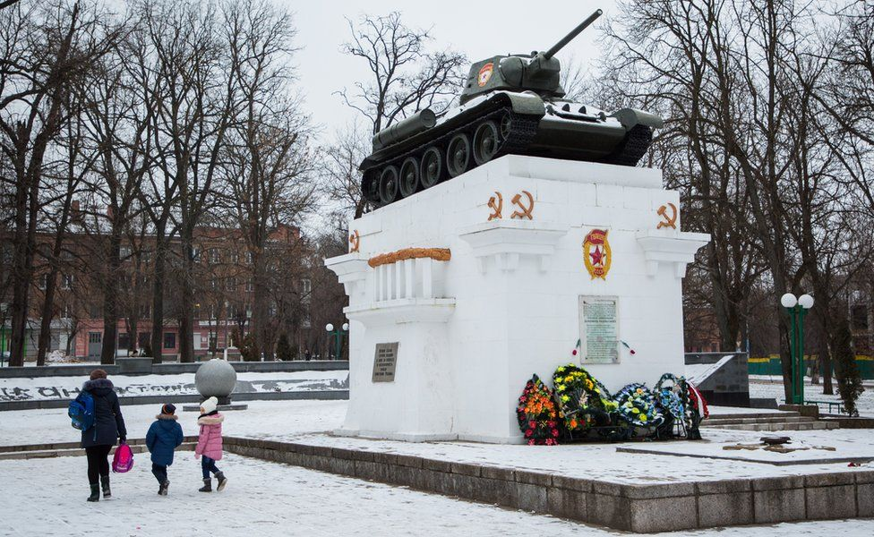 A mother and her two children walk past a Soviet world war two memorial in snowy Kamyanets-Podilskyi