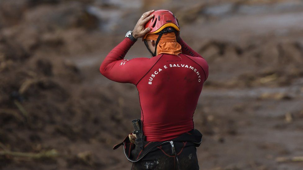 A rescuer holds his head in his hands