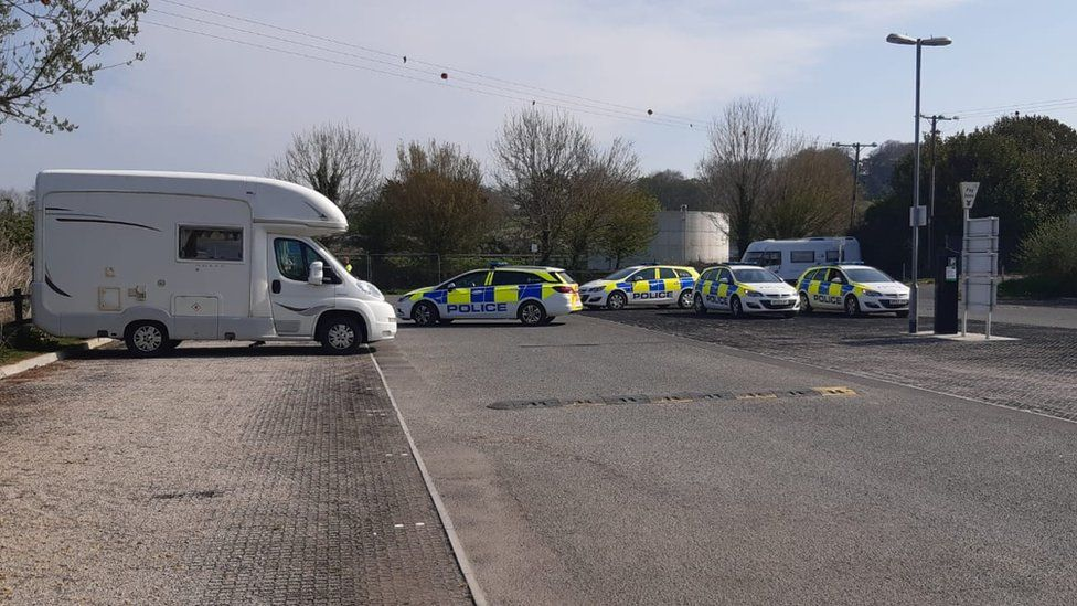 Four police cars and Mimi Gulliford's van in the car park