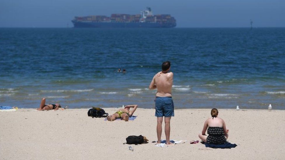 Beachgoers apply sunscreen on a hot day in Melbourne