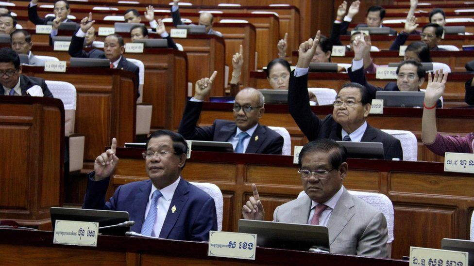 """This handout taken and released on February 20, 2017 by the Cambodia National Assembly shows Cambodia""""s Prime Minister Hun Sen (front L) and other lawmakers voting during the parliament meeting at the National Assembly building in Phnom Penh. They have their right hands raise in the air."""