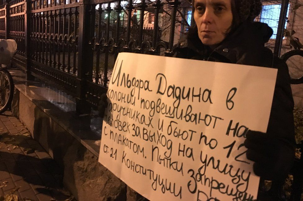 """Woman holding sign saying """"They hang Dadin by his handcuffs and 12 men beat him for taking to the streets with a protest banner. Torture is banned under Article 21 of the Russian constitution"""