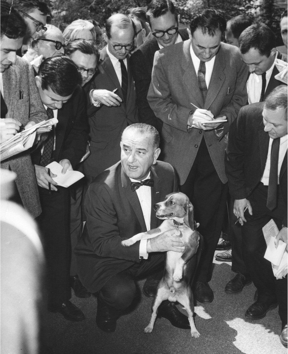 President Lyndon Johnson holds a beagle dog whilst speaking to a group of journalists
