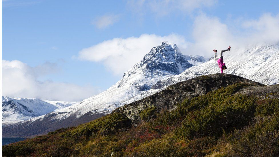 An image made available on 20 March 2017 showing a girl standing on hands with the Torfinnstind Jotunheimen in the background, Vang, Norway, 01 October 2016.