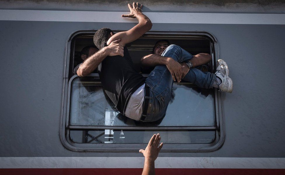 Migrant tries to enter train through the window