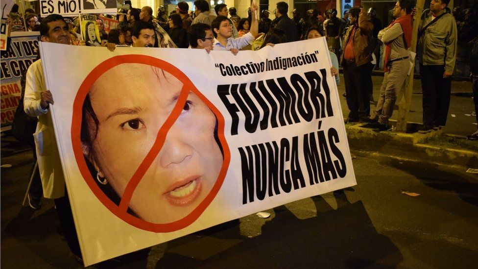 """People attend a march against Keiko Fujimori carrying a sign reading """"Fujimori never again"""""""