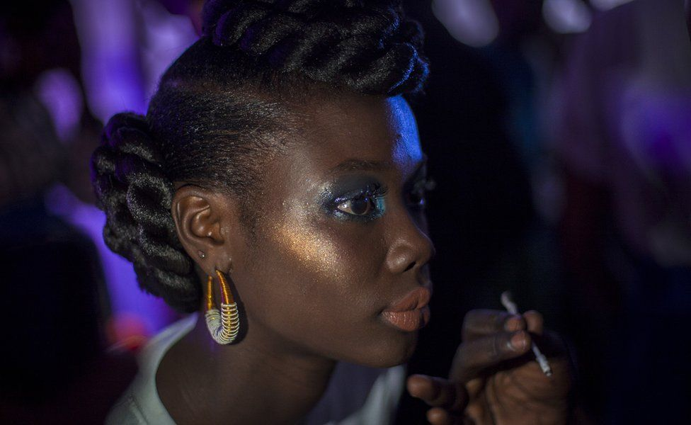 Une mannequin se maquille dans les coulisses de la Semaine de la mode de Dakar, à Dakar, au Sénégal.