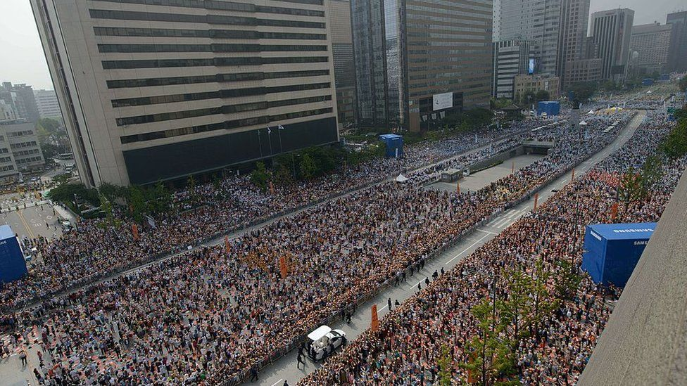 Thousands of South Koreans watch as Pope Francis drives through central Seoul in August 2014