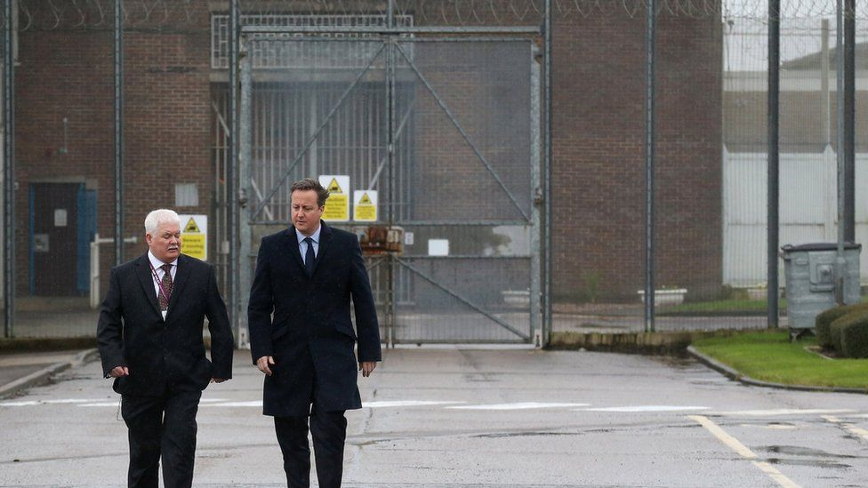 David Cameron is escorted by prison governor Stephen Ruddy (L) as he tours HMP Onley near Rugby