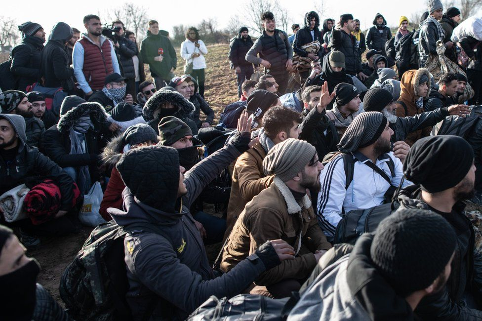 Refugees and migrants sit as they wait near Turkey's Pazarkule border crossing with Greece's Kastanies on 3 March