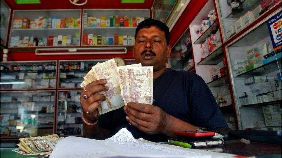 A shopkeeper counts 500 Indian rupee banknotes at a cash counter inside a medicine shop in Agartala, India, November 9, 2016