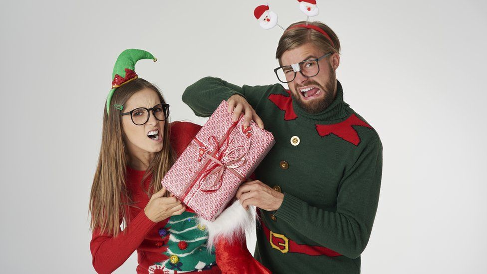 Two people dressed in Christmas clothes fighting over a Christmas present