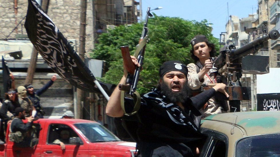 Fighters from Jabhat Fateh al-Sham drive in the northern Syrian city of Aleppo while flying Islamist flags, in 2015