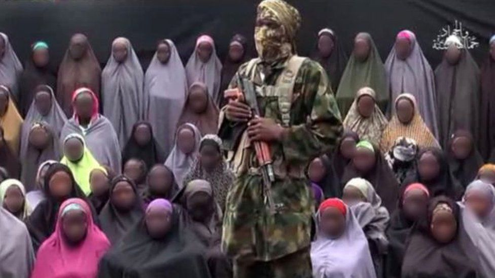 A still from a Boko Haram video showing a militant in front of some of the Chibok girls