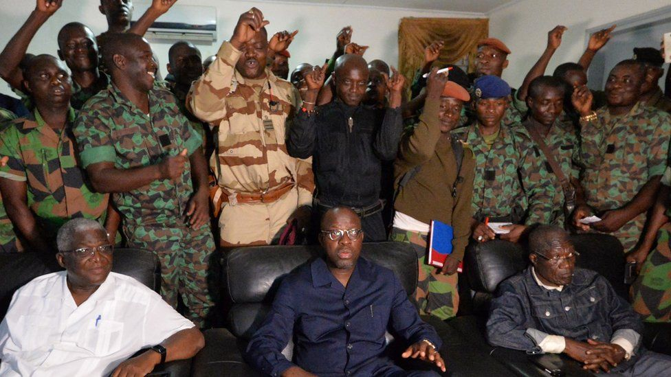 """A delegation of mutinous soldiers stand behind Ivory Coast""""s defence minister Alain-Richard Donwahi (C-front) speaking to journalists after negotiations, on January 7, 2017 in Bouake."""