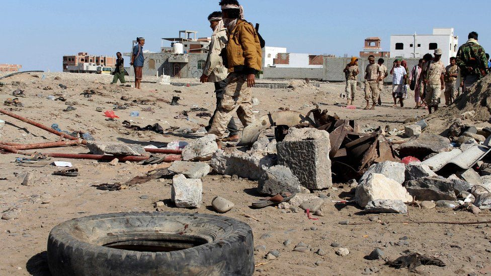 Soldiers gather the site of a suicide bomb at a base in the southern city of Aden, Yemen, 18 December.