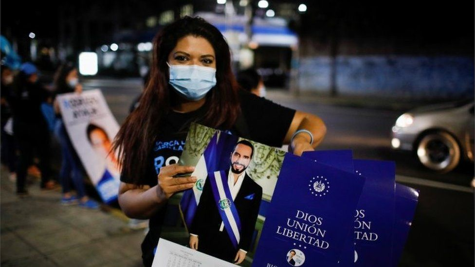A supporter of the Nuevas Ideas political party holds calendars with the picture of El Salvador's President Nayib Bukele as she takes part in a rally during the last day of election campaign in San Salvador, El Salvador, February 24, 2021