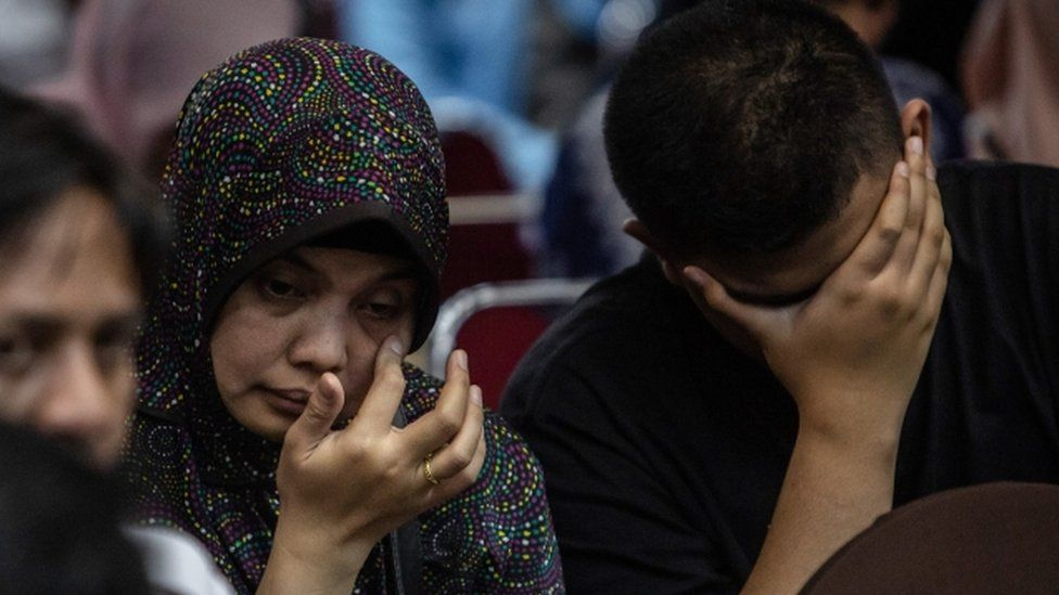 Family of a victim of the Lion Air crash weep at a meeting with authorities