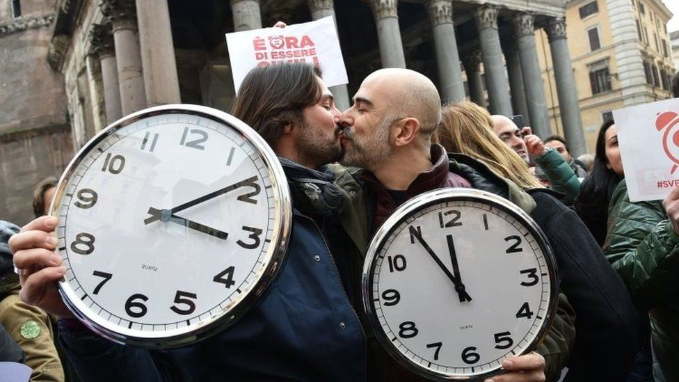 A couple holding alarm clocks kiss in Rome. Photo: January 2016