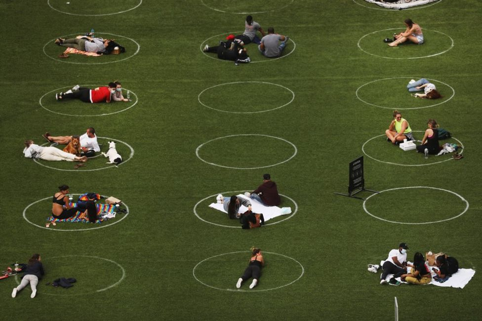 An aerial view showing people relaxing in a park whilst staying designated white circles to ensure social distancing