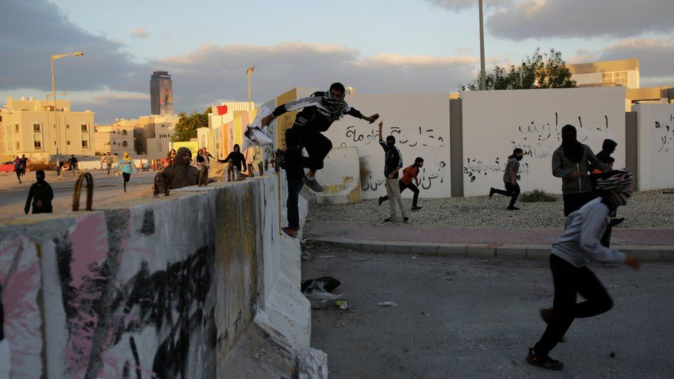 Bahraini protesters jump a cement barricade as police approach near the end of a march denouncing the execution of Saudi Shiite cleric Sheikh Nimr al-Nimr, on Sunday, 3 January 2016, in Daih, Bahrain