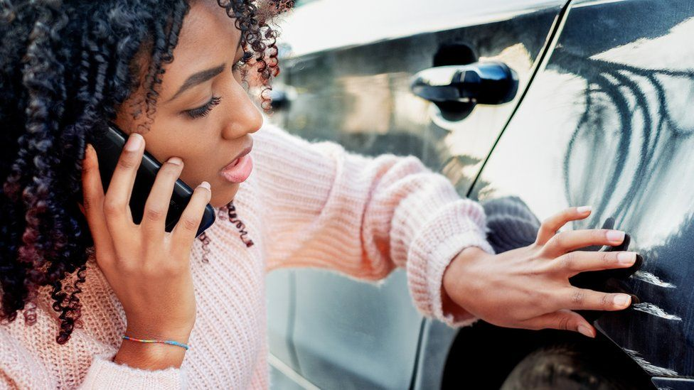 A woman calling her insurer after scratching her car
