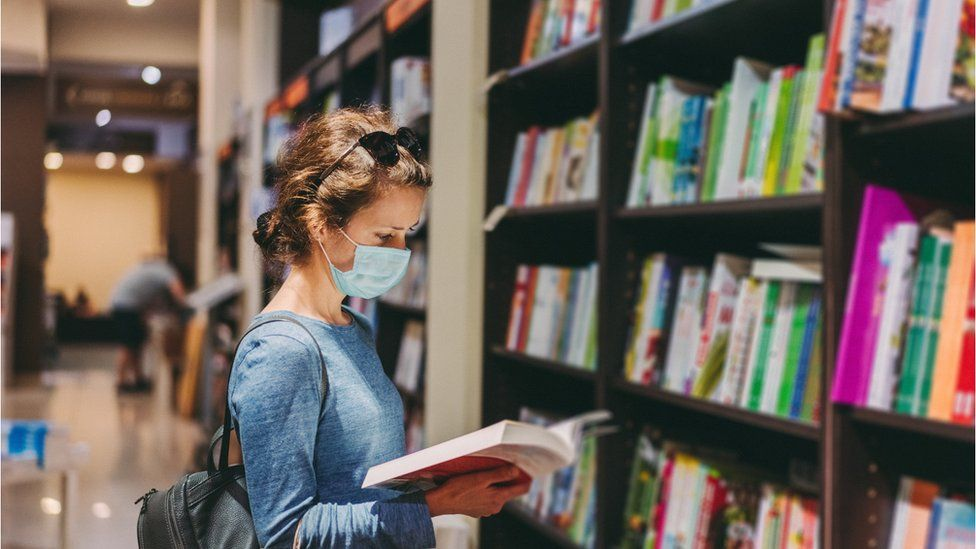 A student wearing a mask in a library